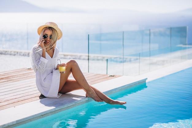 電話を使用してプールサイドでの休暇に若い女性