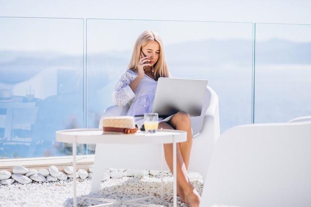 Молодая женщина работает на ноутбуке в отпуске