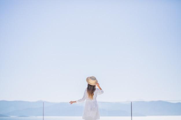 Молодая женщина, стоя сзади и глядя на море