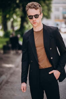 若い男モデルが通りでポーズをとる