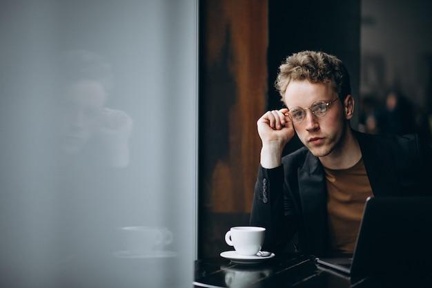 ハンサムな男がカフェでコンピューターに取り組んでいるとコーヒーを飲む