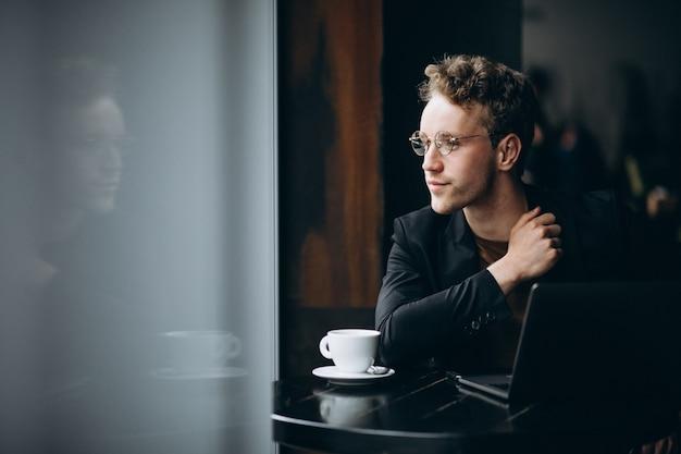 Красивый мужчина работает на компьютере в кафе и пить кофе