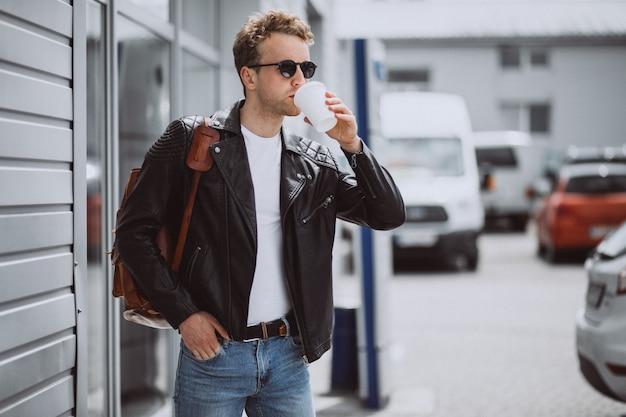通りでコーヒーを飲む若いハンサムな男