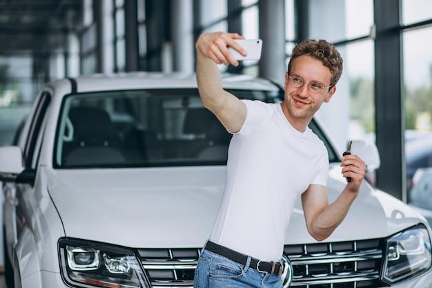 Мужчина ищет машину в автосалоне