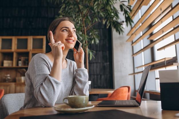 コーヒーを飲みながら、コンピューターに取り組んでいるカフェに座っている女性