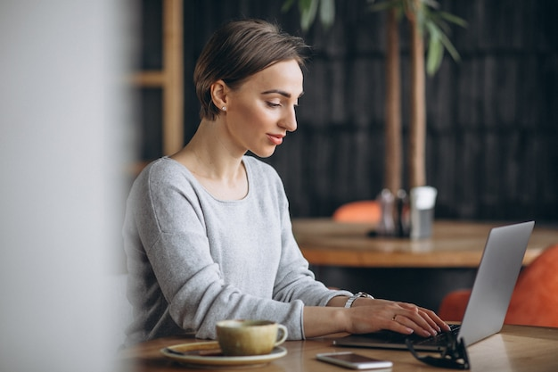 Женщина, сидя в кафе, пить кофе и работает на компьютере
