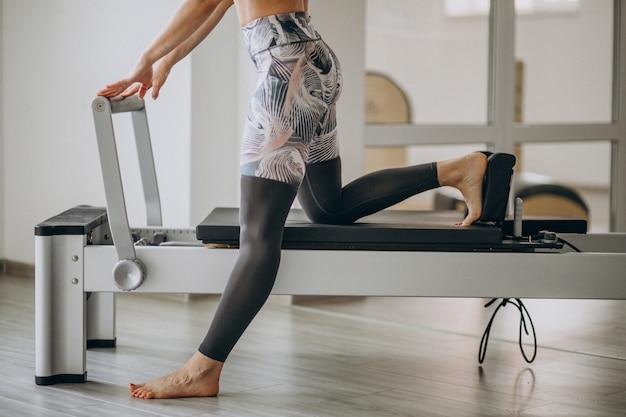 ピラティスリフォーマーでピラティスを練習する女性の足をクローズアップ