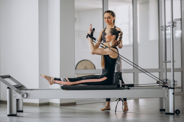 ピラティストレーナーピラティスの練習を持つ女性