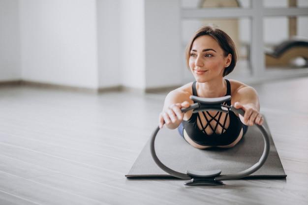 Женщина занимается йогой в тренажерном зале на коврике