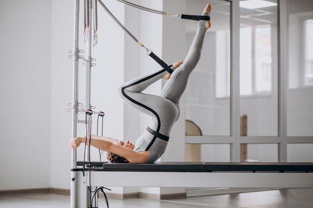 ピラティスリフォーマーでピラティスを練習する女性
