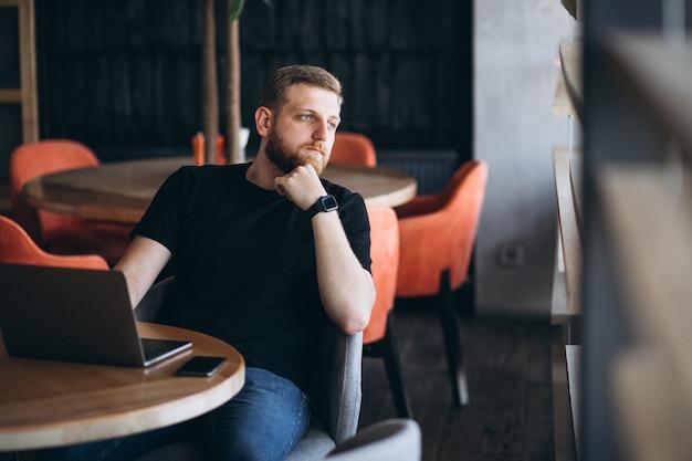 Бородатый мужчина работает на ноутбуке в кафе