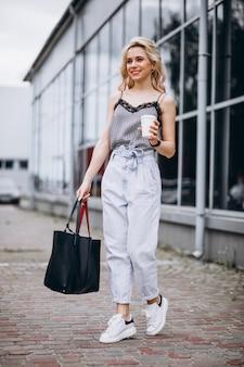 Молодая женщина пьет кофе на улице