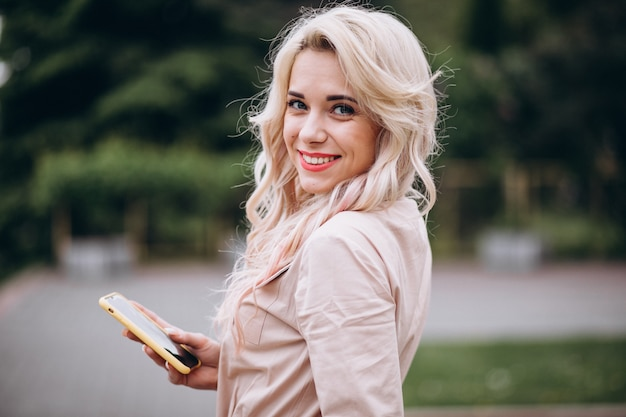 Молодая женщина, с помощью телефона снаружи в парке