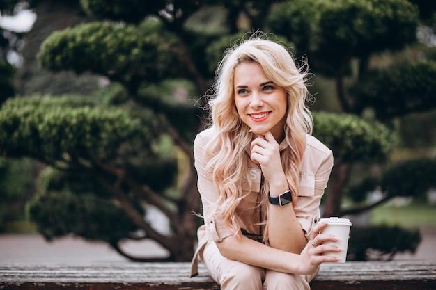 Довольно блондинка пьет кофе