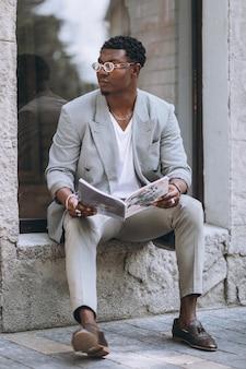アフリカ系アメリカ人の男が雑誌を読む
