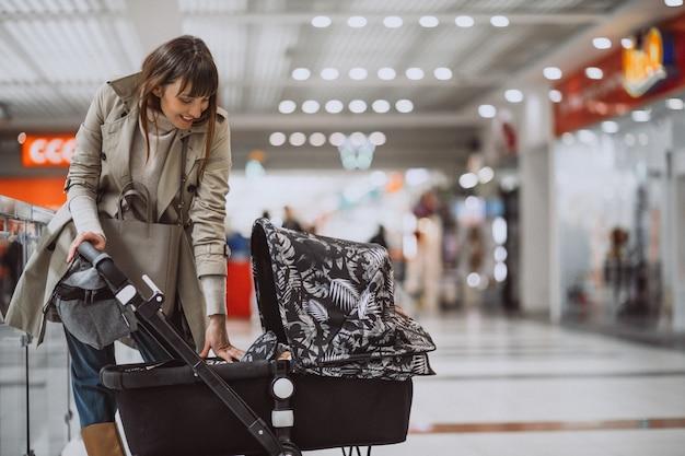 ショッピングモールのベビーカーを持つ女性