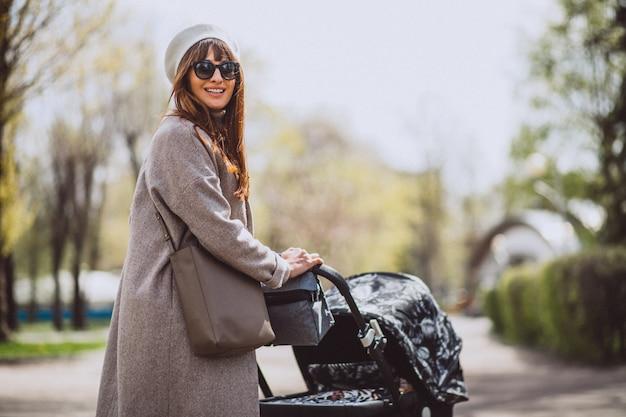 Молодая мать сидит с коляской в парке