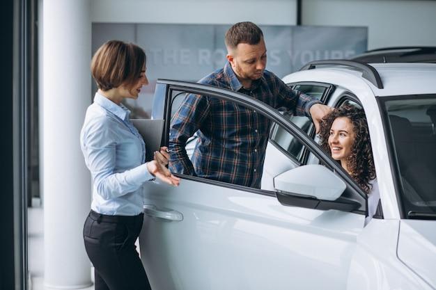 Молодая пара разговаривает с продавцом в автосалоне