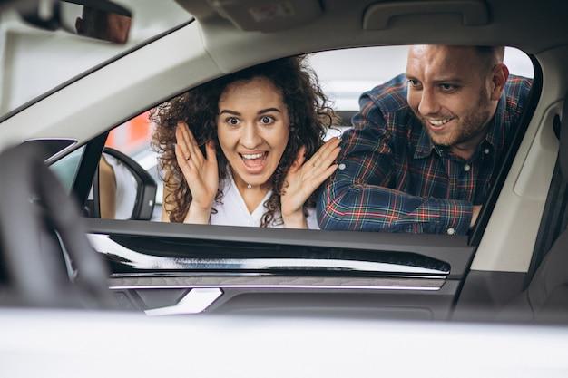 若いカップルが車のショールームで車を選ぶ
