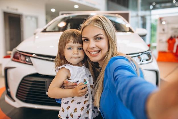 車の前に立っている彼女の小さな娘を持つ母