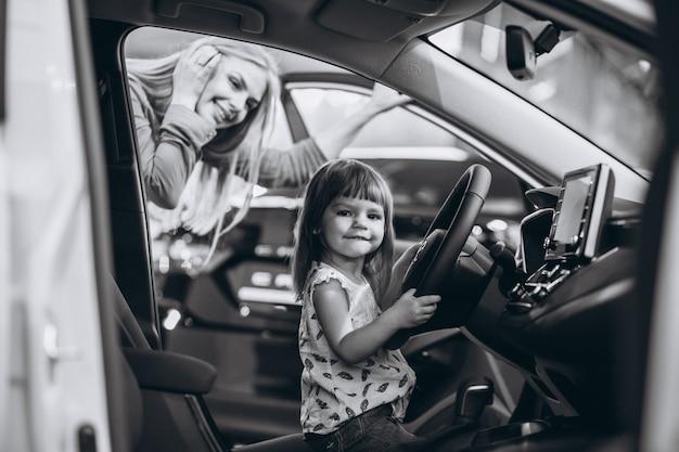 車のショールームで車に座っている小さな娘を持つ母