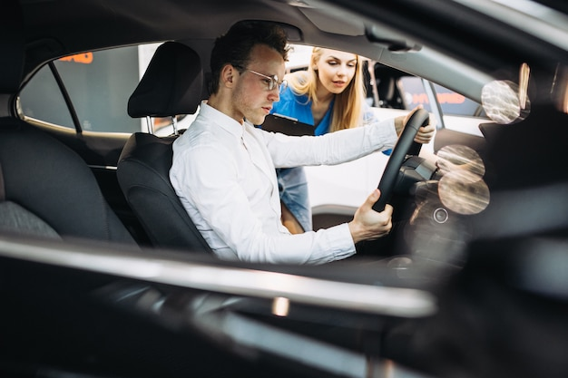 ハンサムなビジネスの男性が車のショールームで車を選ぶ