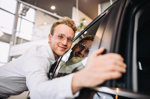 車のショールームで車を抱き締める男