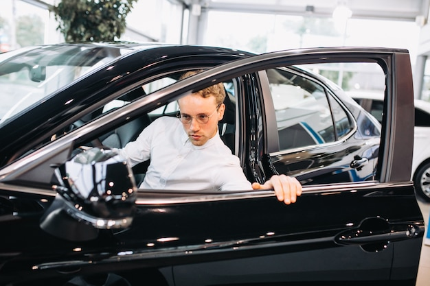 ショールームで車を選ぶハンサムな男