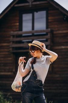 カントリーサイドのフルーツとエコバッグを持つ女性