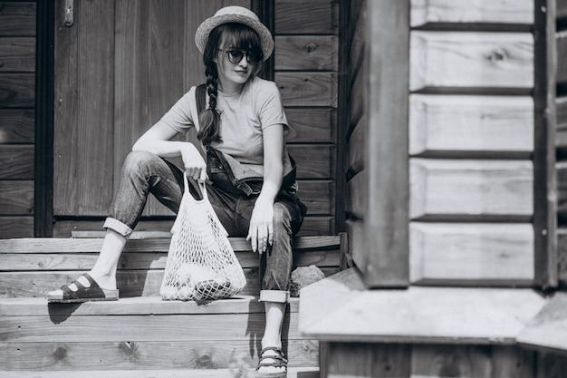 Женщина с эко сумкой с фруктами в сельской местности