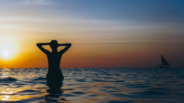 Женщина в океане во время заката