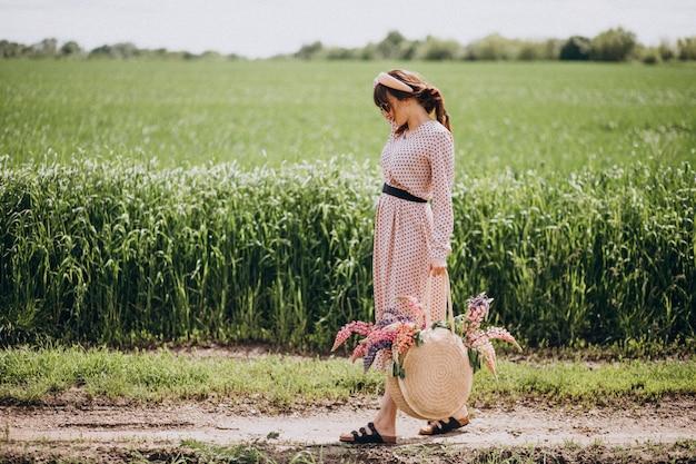 ルピナスのフィールドを歩く婦人
