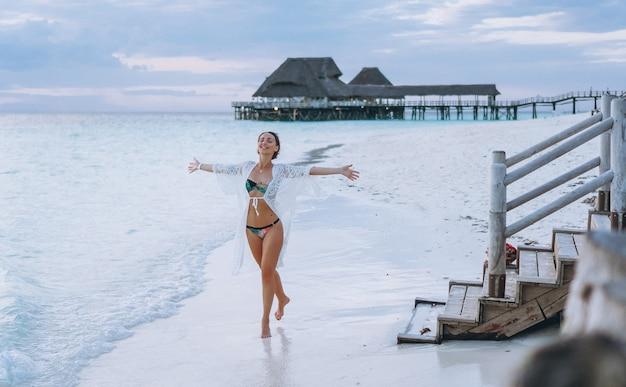 Красивая женщина в купальных костюмах на берегу океана