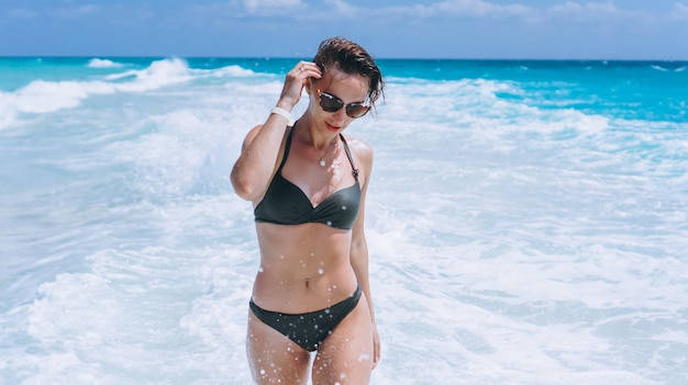 水着でセクシーな女性は海の水でビキニを着用