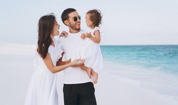 海沿いの休暇に小さな娘と若い家族