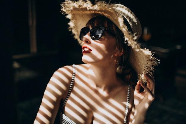 日陰の下に帽子を持つ女性