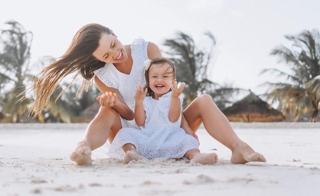 Молодая мать с маленькой дочерью на пляже у океана