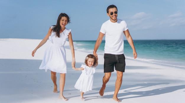 Молодая семья с маленькой дочкой на отдыхе у океана