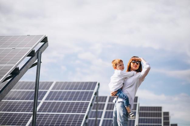 太陽電池パネルで彼女の幼い息子を持つ母