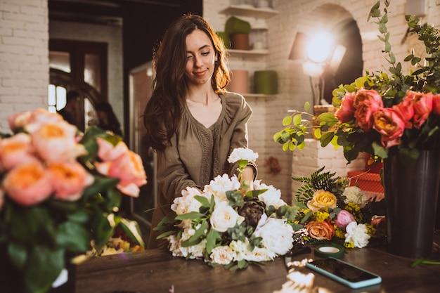 花の世話をして彼女自身の花屋で女性の花屋