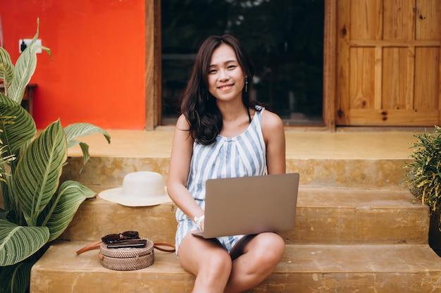 アジアの女性の休暇にラップトップに取り組んで、階段の上に座って