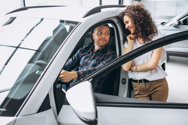 若い家族が車のショールームで車を選ぶ