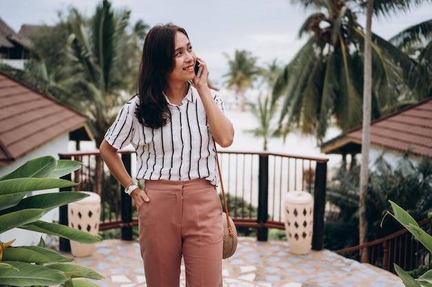 Азиатская бизнес-леди на каникулах говоря на телефоне
