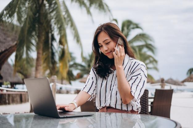 アジアの女性が休暇にラップトップに取り組んで