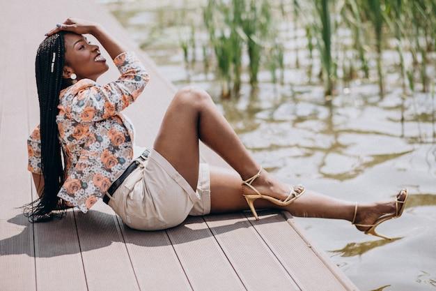 公園の湖のそばに座っているスタイリッシュなアフリカ系アメリカ人女性