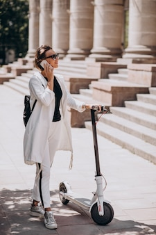 Молодая женщина езда скоттер возле здания университета и с помощью телефона