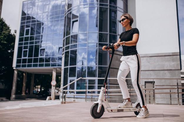 超高層ビルでスコッターに乗る若い女性