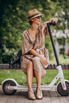 Молодая женщина езда скутер в парке, сидя на скамейке