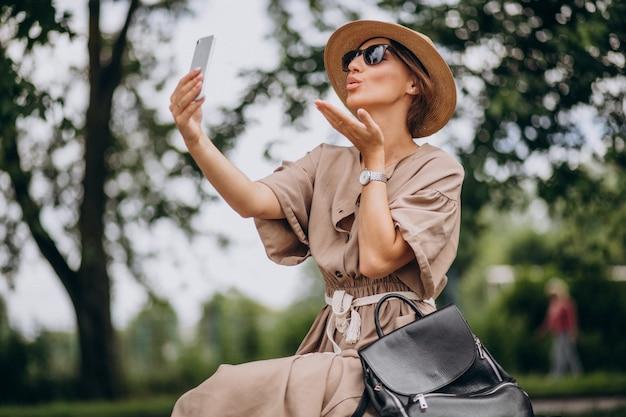 Парк молодой женщины сидя используя телефон