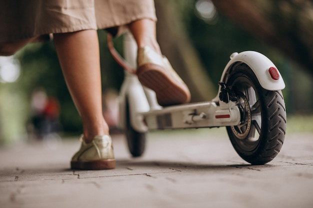 Молодая женщина езда скутер в парке ноги крупным планом